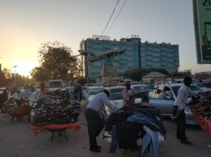 Hargeisa at dawn. Shoe vendors, a shot-down MIG and the modern glass-facade skyscrapers of the capital, by Sascha Duerkop.